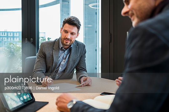 Male entrepreneur and colleague working with digital tablet at work place - p300m2273896 by Daniel Ingold