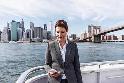 USA, Brooklyn, portrait of  businesswoman standing on boat looking at cell phone - p300m1205355 by Uwe Umstätter