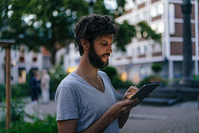 Man looking at phablet in the city at dusk - p300m1535425 by Kniel Synnatzschke