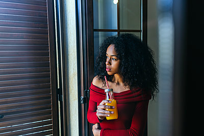 Young woman with beverage looking out of window - p300m1562695 by Kiko Jimenez