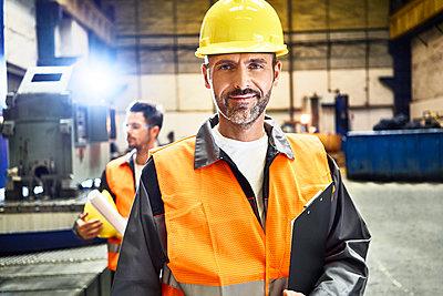 Portrait of smiling man wearing protective workwear in factory - p300m2059892 by Bartek Szewczyk
