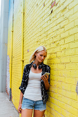 Young woman checking cell phone at yellow brick wall - p300m2069470 by Boy photography