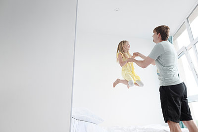 Father and jumping daughter in bedroom - p300m2275115 by Ekaterina Yakunina