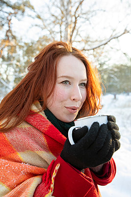 Redhead woman holding coffee while looking away during winter - p300m2287656 by Frank van Delft