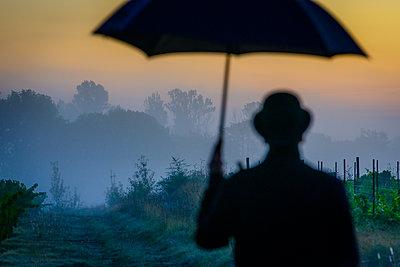 Man with hat and umbrella - p829m2295672 by Régis Domergue