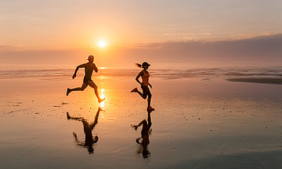 Athletes couple running on the beach at sunset - p300m1166502 by Marco Govel