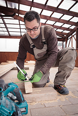 Roof insulation, worker sawing woodbar - p300m2083896 by Sebastian Dorn