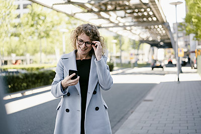 Smiling mature businesswoman looking at  smartphone - p300m2132054 by Kniel Synnatzschke