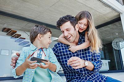 Südafrika, Western Cape, Yzerfontein, Immobilie, modernes Haus, Vater mit Tochter und Sohn, Immobilienmodell, Haus, Spielzeughaus, Familie - p300m2286933 von Roger Richter