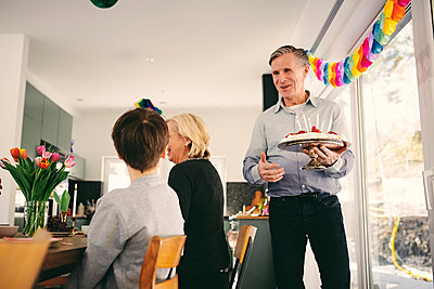 Boy looking at grandfather holding birthday cake in party - p426m1580213 by Maskot