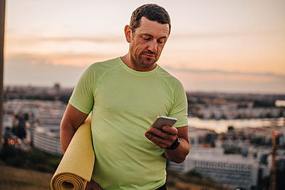 Mature male athlete using mobile phone against sky during sunset - p426m2270867 by Maskot
