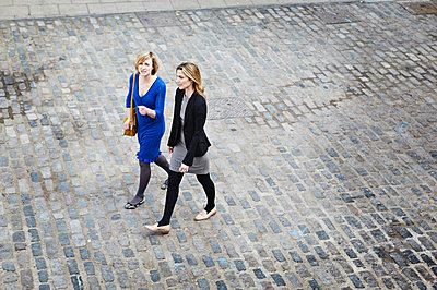 Businesswomen walking on cobbled street, high angle - p429m803584f by Liam Norris