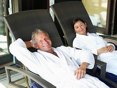 Aelteres Paar sitzt in weissen Bademaenteln auf Liegestuehlen  - p6430342f von senior images RF