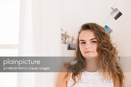 Portrait smiling teenager girl indoor by polaroid photo wall - p1166m2192014 by Cavan Images