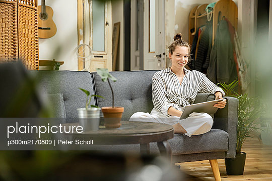 Young woman sitting at home on couch, using digital tablet - p300m2170809 by Peter Scholl