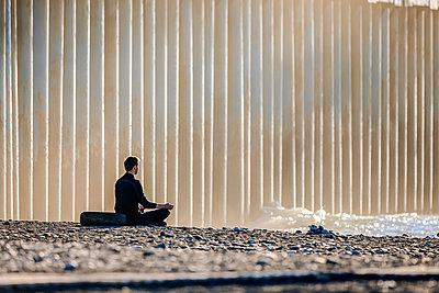 Mann meditiert auf dem Steinstrand - p1108m2245514 von trubavin