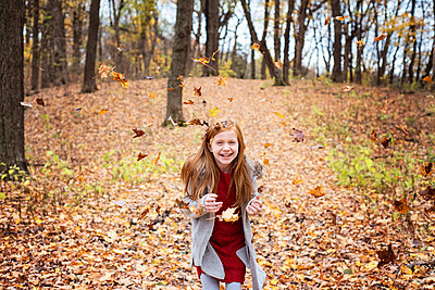 Young Red Hair Girl Playing Outside in Fall Leaves - p1166m2147073 by Cavan Images
