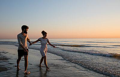 Junges Paar - Sonnenuntergang am Strand - p1212m1168724 von harry + lidy