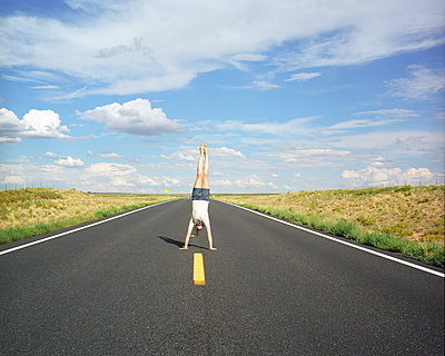 Girl doing a headstand in the middle of an American road - p1610m2182264 by myriam tirler