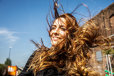 Portrait of smiling woman with blowing hair - p300m2005635 by Jo Kirchherr