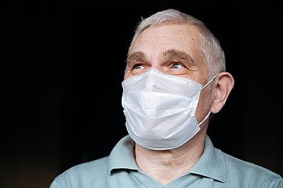 Portrait of senior man wearing a mask at home - p300m2180171 by Ekaterina Yakunina