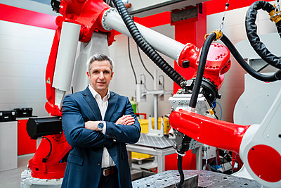 Male entrepreneur with arms crossed standing at robotics in factory - p300m2264790 by Daniel Ingold