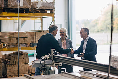 Owner shaking hands with businessman standing by colleague in lumber industry - p426m1537015 by Maskot