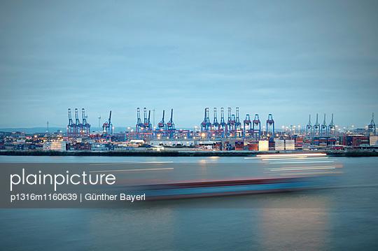 Schiff fährt vor Hamburger Hafen bei Dämmerung, Blick von Docklands, Hansestadt Hamburg, Deutschland - p1316m1160639 von Günther Bayerl