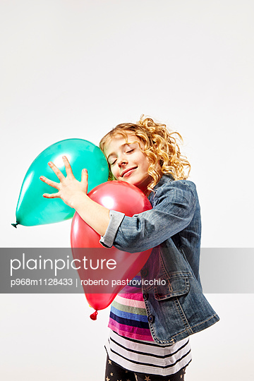Blonde girl holding two colourful balloons - p968m1128433 by Roberto Pastrovicchio
