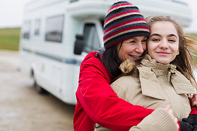 Affectionate mother and daughter in warm clothing hugging outside motor home - p1023m2024310 by Sam Edwards