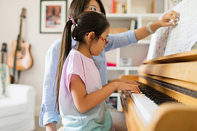 Mother and daughter playing piano - p1023m2033702 by Sam Edwards