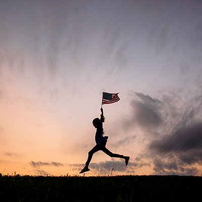 Silhouette girl with American flag running on field against sky - p1166m1182588 by Cavan Images