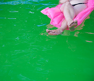 Woman floating in paddling pool full of alga - p1231m1208284 by Iris Loonen