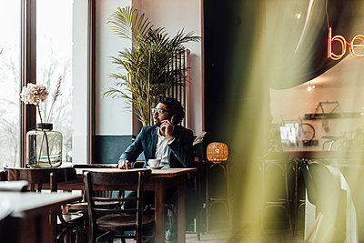 Male professional talking on smart phone while sitting on cafe - p300m2287463 by Gustafsson