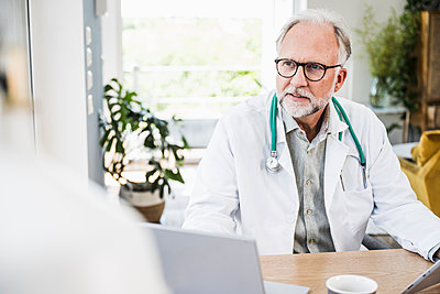 Mature male doctor looking away at desk - p300m2293792 by Uwe Umstätter