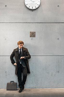 Sweden, Skane, Malmo, Businessman checking time on railroad station platform - p352m1127139f by Viktor Holm