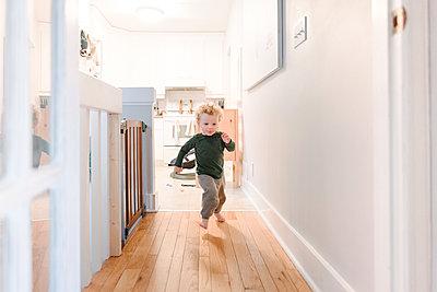 Boy running along corridor - p924m2074195 by Viara Mileva