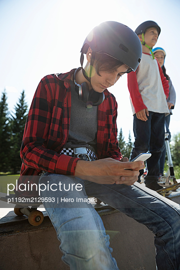 Teenage boy with skateboard using smart phone in sunny skate park - p1192m2129593 by Hero Images