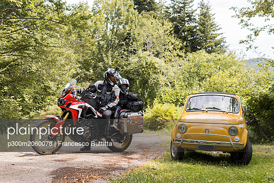 Father and son on a motorbike trip on a country road stopping beside compact car - p300m2060078 by Francesco Buttitta
