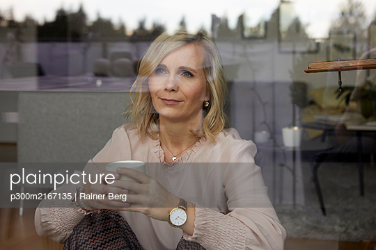 Portrait of blond woman behind windowpane at home - p300m2167135 by Rainer Berg