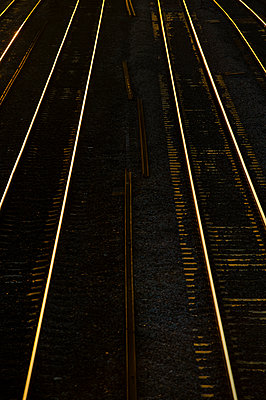 Rail lines lit by the late evening light as it reflects from the track - p1057m1475312 by Stephen Shepherd