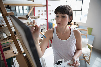 Focused female painter painting at canvas in art studio - p1192m1490236 by Hero Images
