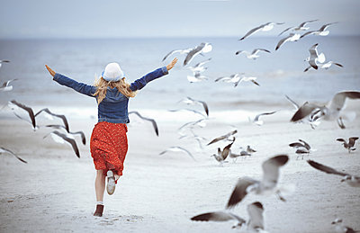 Woman running next to the ocean surrounded by flying seagulls - p1577m2150310 by zhenikeyev