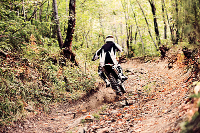 Italy, Motocross biker rinding in Tuscan forest - p300m1449390 by Francesco Morandini