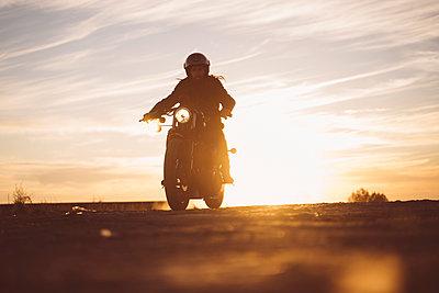 Silhouette of man riding custum motorcycle at sunset - p300m2081286 by Oscar Carrascosa Martinez