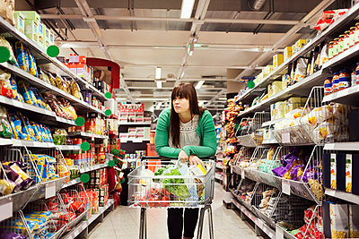 Young woman leaning on shopping cart at supermarket aisle - p426m1017978f by Maskot