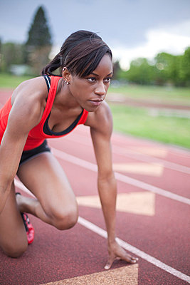 Young female sprinter in starting stance - p4342612f by Alin Dragulin