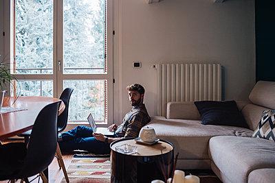 Mid adult man sitting on living room floor using laptop, portrait - p924m2097305 by Eugenio Marongiu