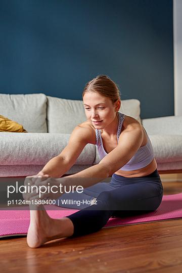 Junge Frau macht eine Stretching Übung  - p1124m1589400 von Willing-Holtz