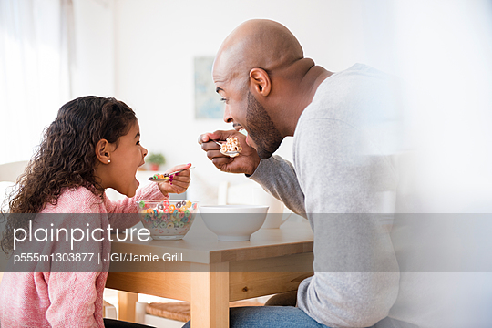 Father and daughter eating cereal at table - p555m1303877 by JGI/Jamie Grill
